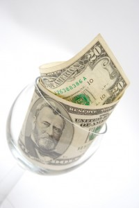Twenty dollar bills in a wine glass